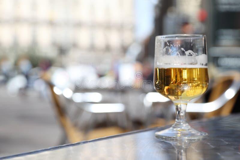 半完成杯啤酒在灰色窗台站立。 库存照片