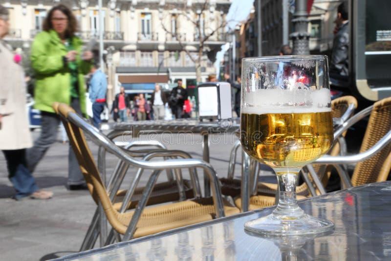 半完成杯啤酒在街道咖啡馆的桌上站立 图库摄影