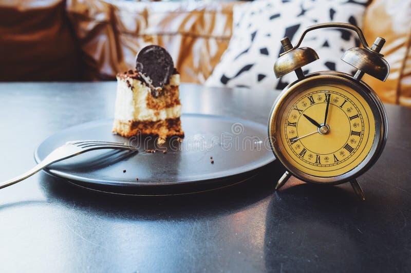 半巧克力蛋糕和闹钟在黑桌上 库存照片