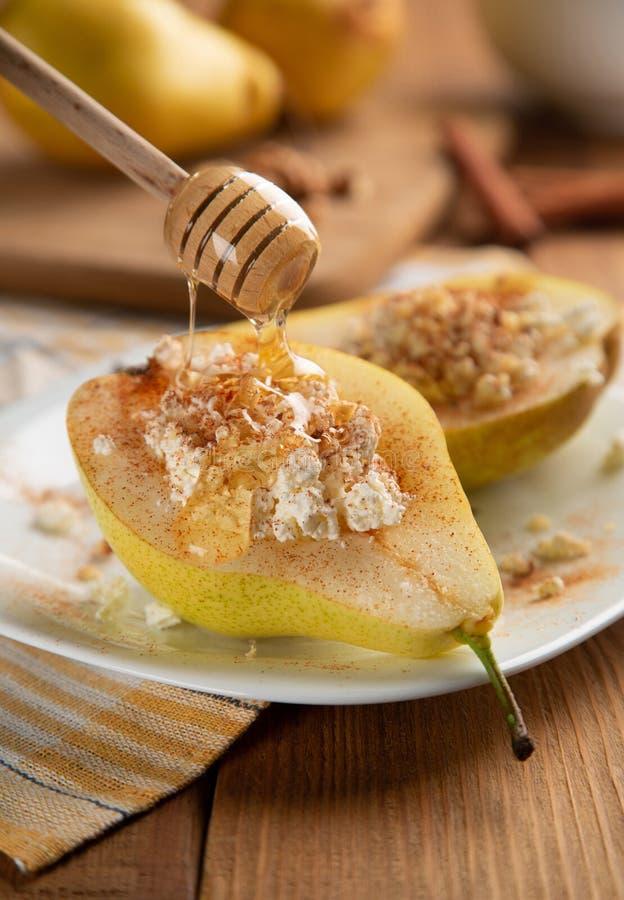 半梨用酸奶干酪、坚果、蜂蜜和桂香在白色 图库摄影