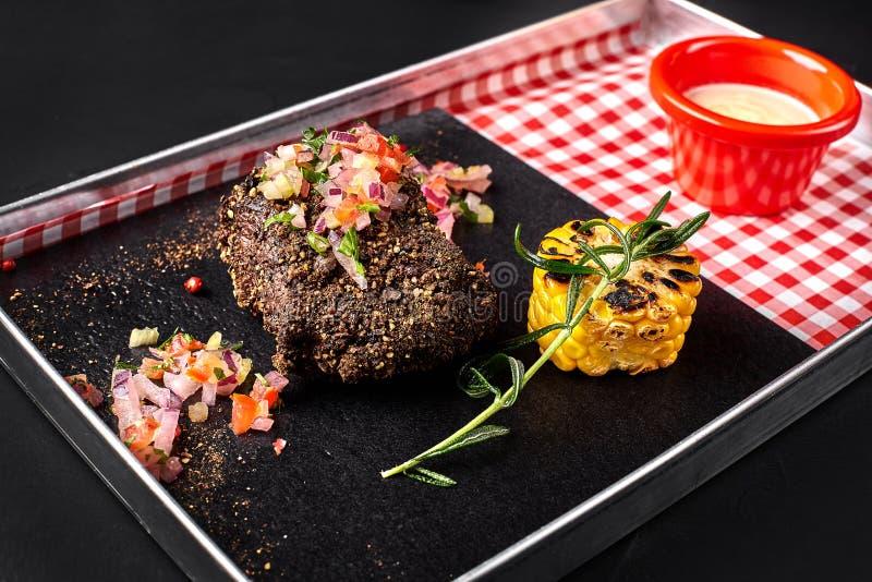 半生半熟烤牛排Ribeye用玉米、迷迭香、葱和白汁在一个金属盘子在黑背景 免版税图库摄影