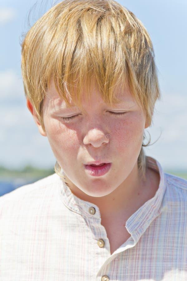 半眯着眼睛看的白肤金发的男孩画象在河附近的 免版税库存照片