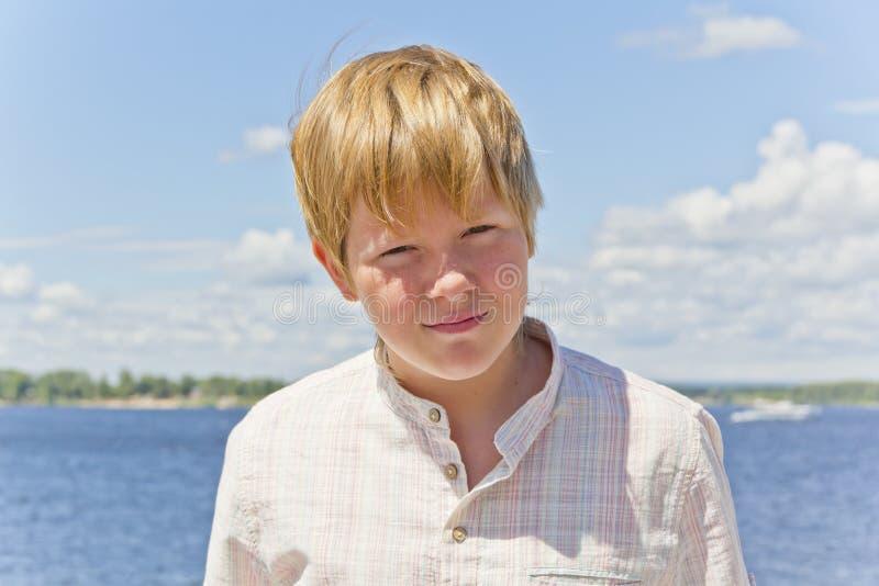 半眯着眼睛看的白肤金发的男孩画象在河附近的 库存照片