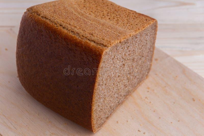半砖布朗酿造了从黑麦面粉的面包,在木书桌上 免版税库存照片