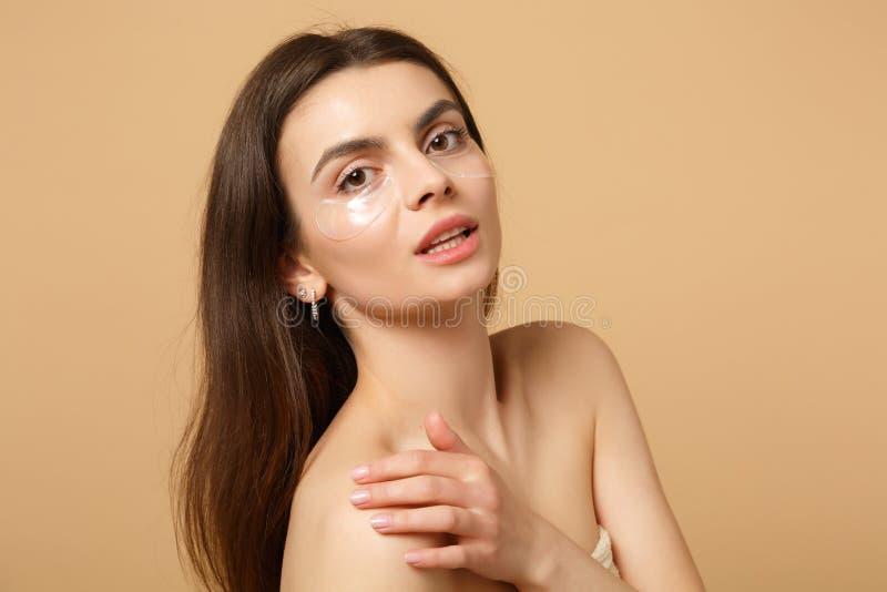 半赤裸妇女20s的关闭有完善的皮肤的,裸体组成补丁在被隔绝的眼睛下在米黄淡色墙壁 库存图片