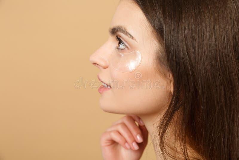 半赤裸妇女20s的关闭有完善的皮肤的,裸体组成补丁在被隔绝的眼睛下在米黄淡色墙壁 免版税库存图片