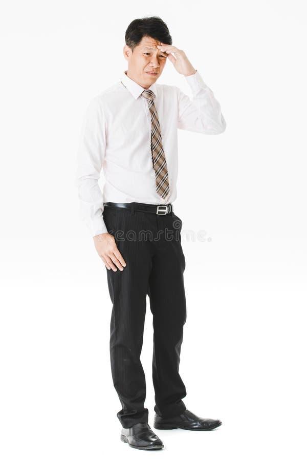 半身画象中间变老,英俊,亚洲,商人,在白色衬衫,镶边领带 遭受深刻偏头痛,鬼脸 免版税库存照片