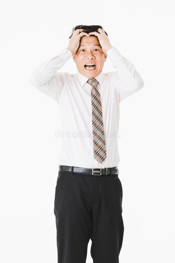 半身画象中间变老,英俊,亚洲,商人,在白色衬衫,镶边领带 遭受深刻偏头痛,鬼脸 图库摄影