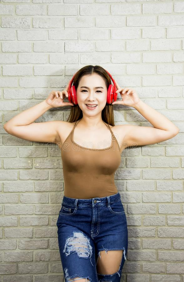 半身画象亚裔妇女愉快地微笑并且喜欢听到音乐,佩带的红色耳机,穿有牛仔布的棕色背心 图库摄影