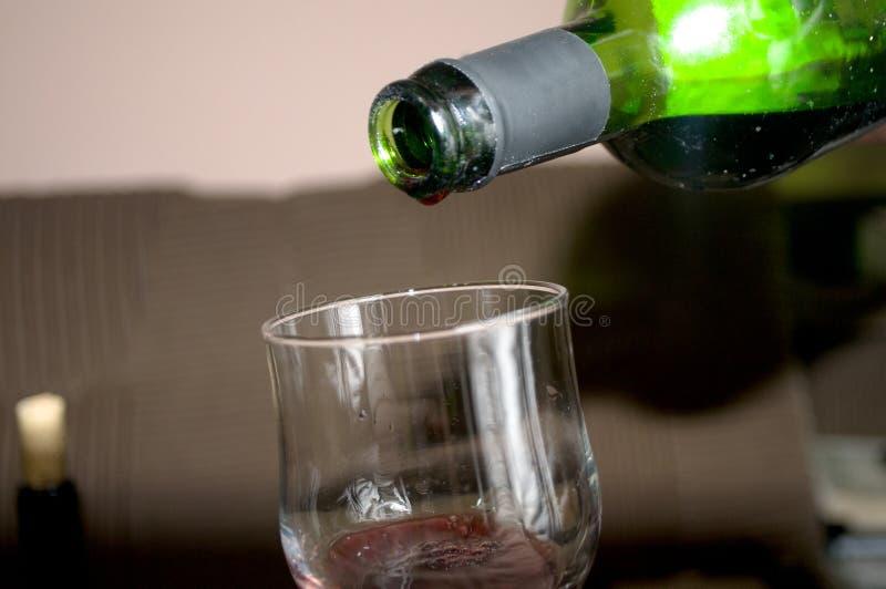 半满的杯新鲜的可口红葡萄酒,瓶在与心脏的背景中 免版税图库摄影