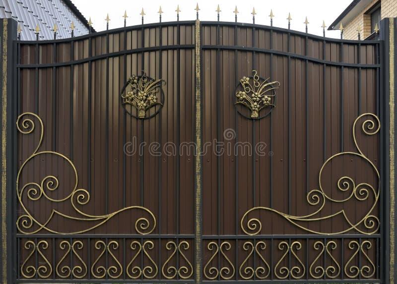 华丽的铁艺栅门,涂成红褐色和金色 免版税库存照片