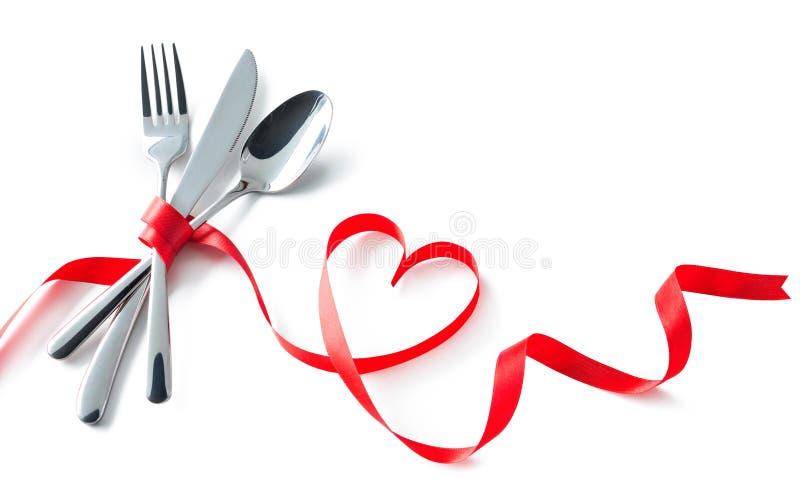 华伦泰叉子,刀子,匙子,与红色丝带心脏s的银器 免版税库存图片