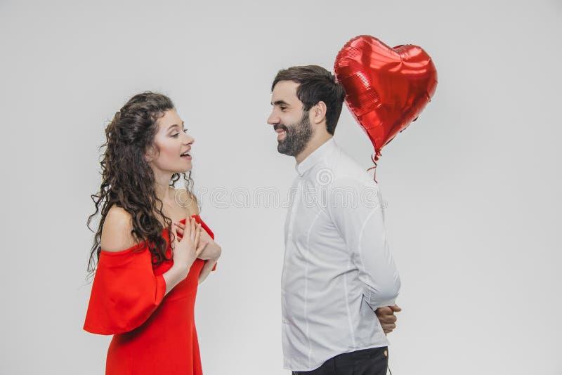 华伦泰夫妇 举行心形的气球和亲吻的秀丽女孩和她英俊的男朋友 愉快快乐 免版税图库摄影