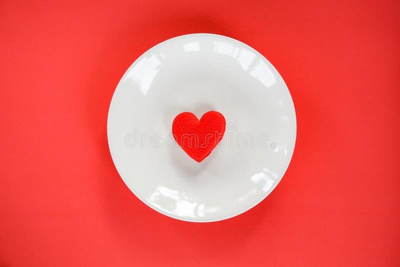 华伦泰晚餐浪漫爱烹调概念/红心在白色板材的食物和爱 免版税库存图片