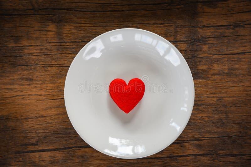 华伦泰晚餐浪漫爱食物和喜爱烹调在白色用红心装饰的板材浪漫桌设置的红心 免版税图库摄影