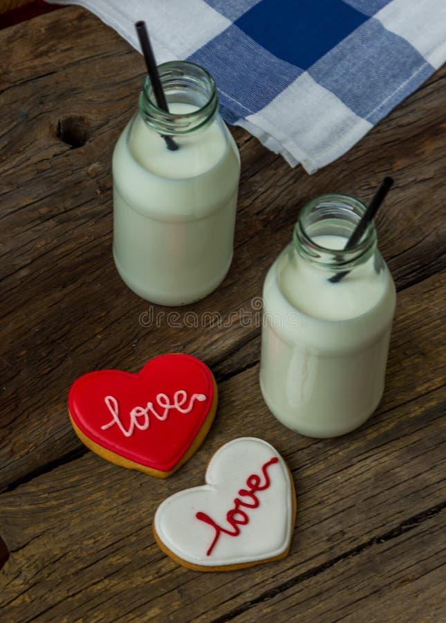 华伦泰曲奇饼和牛奶在一个瓶在木背景 库存照片