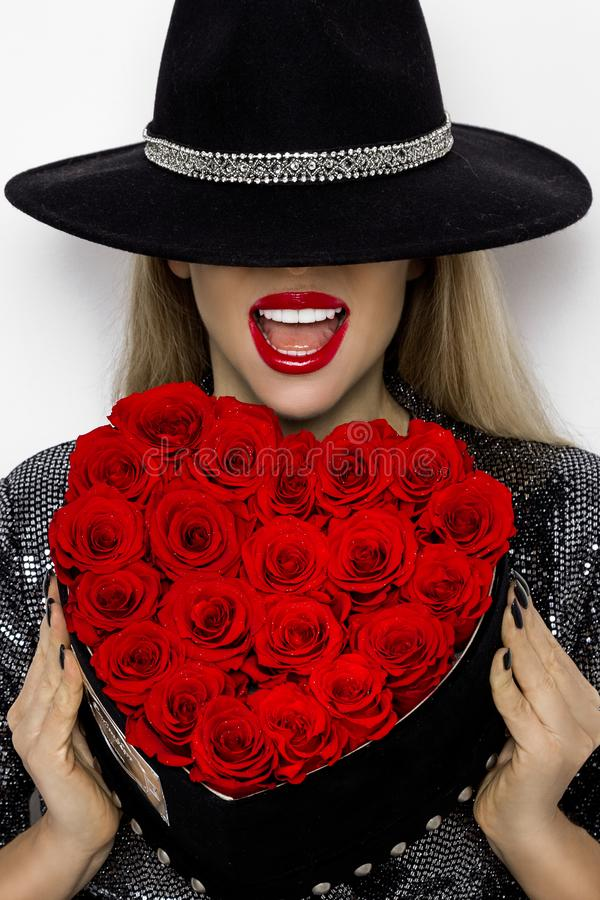 华伦泰有红心玫瑰的秀丽女孩 一个年轻女性模型的画象与礼物和帽子的,隔绝在背景 免版税库存照片