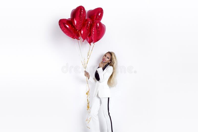 华伦泰有红色气球画象的秀丽女孩,隔绝在背景 一套典雅的无尾礼服的美丽的愉快的年轻女人 免版税库存照片