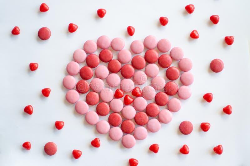 华伦泰桃红色` s的天和红色心脏由巧克力和糖果制成 图库摄影