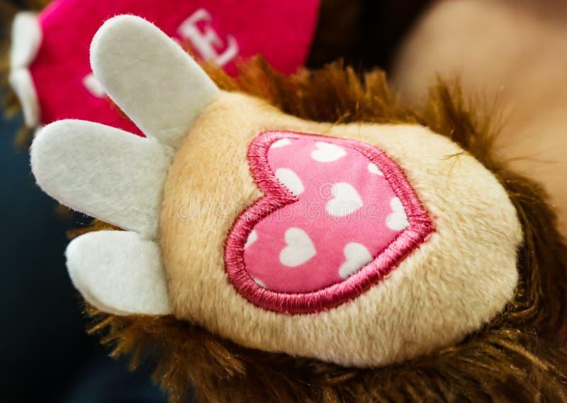 华伦泰爪子-与绣的桃红色织品心脏在一个被充塞的玩具的脚有说在backgrou的爱的被充塞的心脏的 库存照片