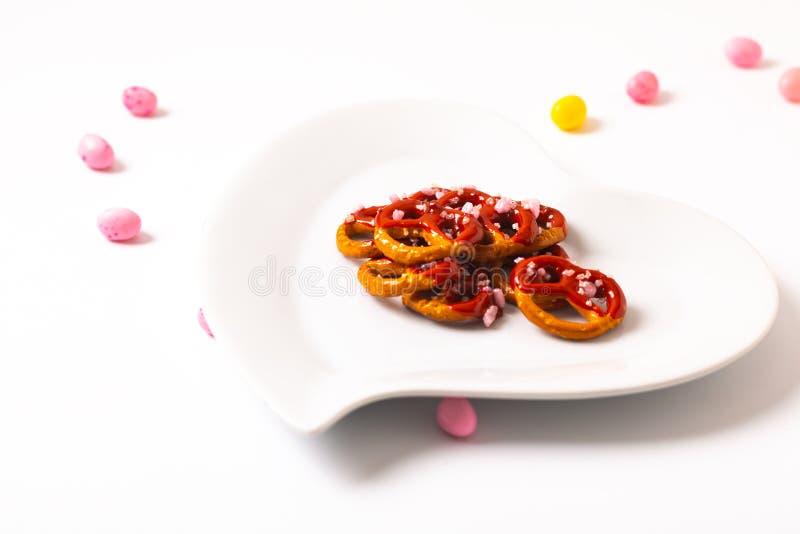 华伦泰的想法对待椒盐脆饼在陶瓷心形板材的垂度巧克力在白色背景与拷贝空间 库存照片