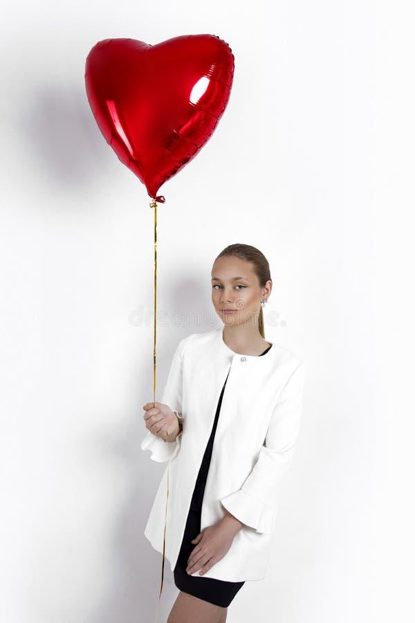 华伦泰秀丽少女,有红色气球画象的少年,隔绝在背景 免版税库存图片
