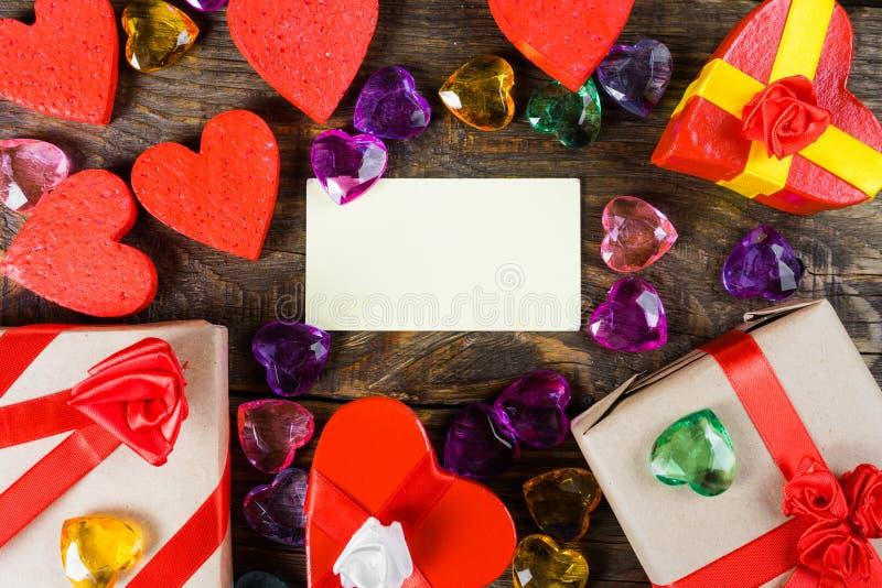 华伦泰` s与贺卡、心脏装饰和小礼物的天背景在木桌上 与拷贝空间的顶视图 免版税库存照片