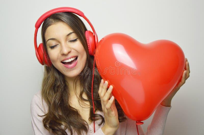 华伦泰` s天爱女孩概念 有红色耳机的逗人喜爱的热心者女孩听到他的心脏音乐的  愉快的妇女年轻人 库存图片