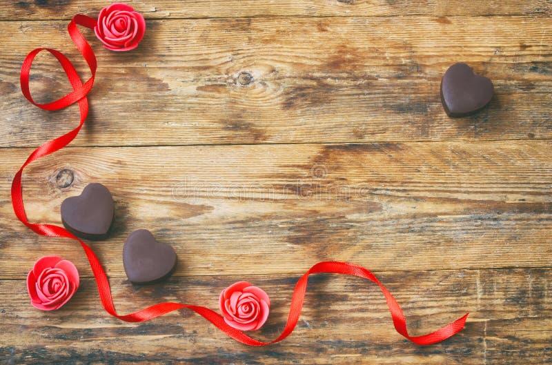 华伦泰` s天贺卡,牛奶巧克力心脏形状,上升了 免版税库存图片