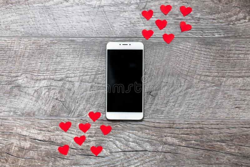 华伦泰` s天,在木灰色背景的电话,与红色心脏,爱,两个之间的连接,适用于advertiseme 免版税库存照片