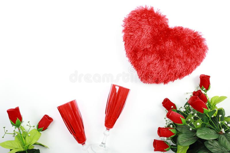 华伦泰` s日概念 有红色香槟在白色背景隔绝的玻璃和英国兰开斯特家族族徽的心形的枕头 免版税库存图片