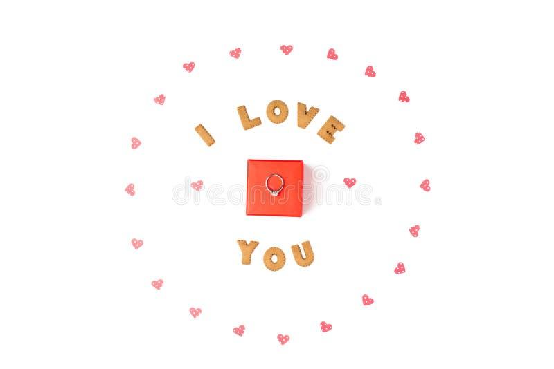 华伦泰` s日概念 爱,框架的声明由纸心脏做成 在有圆环的中心红色礼物盒 平的位置,顶视图 免版税库存照片