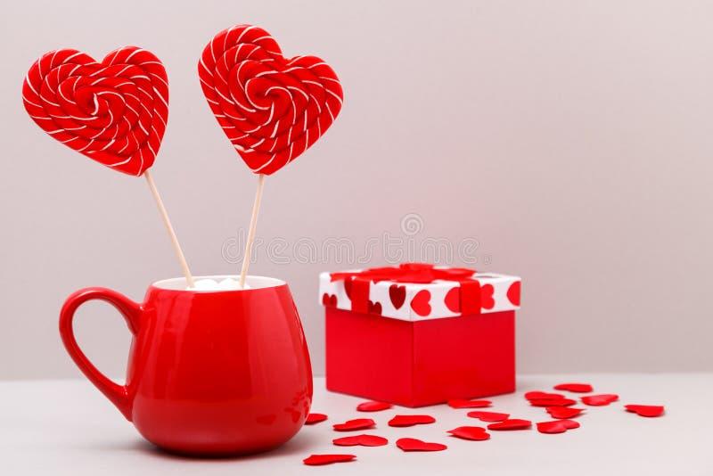 华伦泰` s日背景 在一红色杯的两糖果心脏和驱散在浅灰色的背景的小心脏 免版税库存照片
