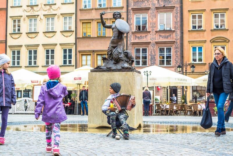 """华沙,波兰†""""2017年5月07日:孩子在街道音乐家附近跑在老镇在华沙在美人鱼雕塑附近 免版税库存照片"""