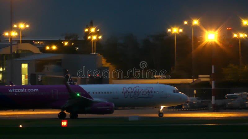 华沙,波兰- 2017年9月14日 乘出租车在机场的Wizz空气商业飞机在晚上 库存图片