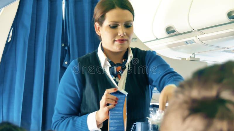 华沙,波兰- 2017年12月25日 空服员供食饮料给KLM班机的乘客 库存照片