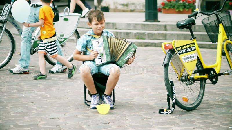 华沙,波兰- 2017年6月10日 播放在街道上的小男孩手风琴 免版税图库摄影