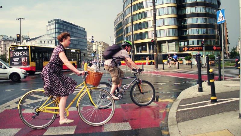 华沙,波兰- 2017年7月11日 骑她的经典自行车的少妇在城市 现代都市街道交通 免版税库存照片
