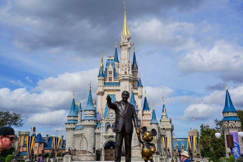 华特・迪士尼和米老鼠在Cinderellas城堡前面的伙伴雕象 免版税库存照片
