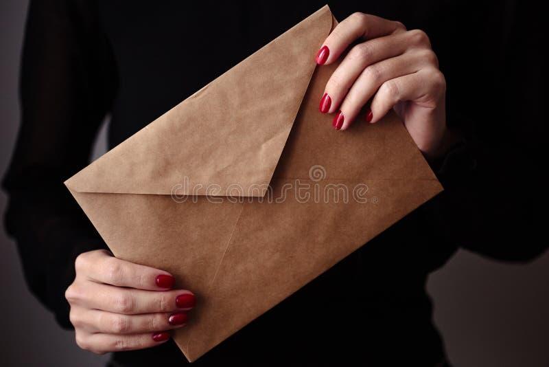 华美的修指甲,经典红色指甲油,特写镜头照片 女性手拿着一个工艺信封 免版税图库摄影