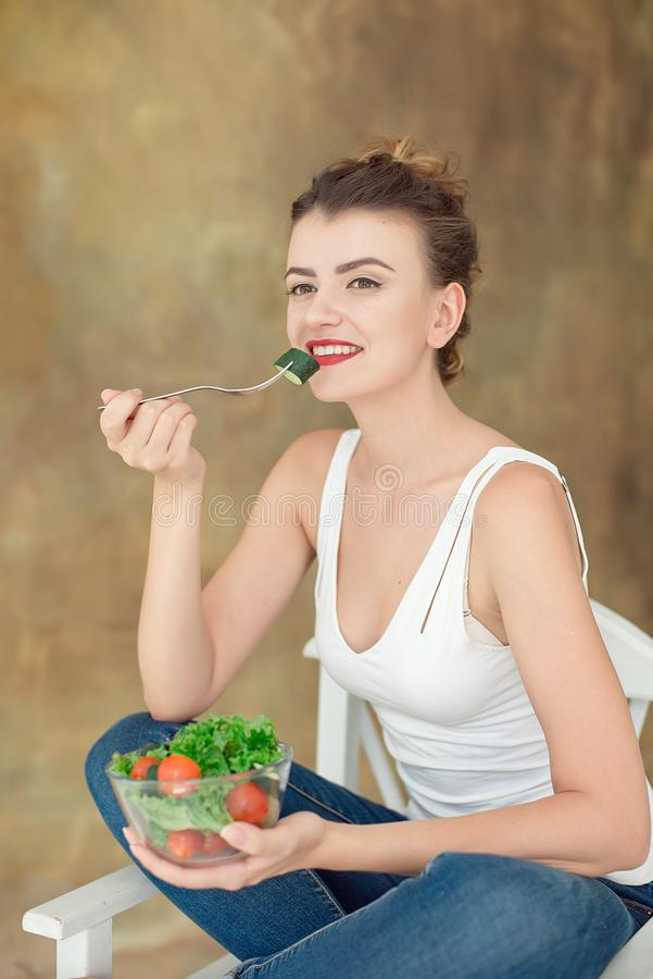 华美的健康妇女坐吃芝麻菜,有机蕃茄,在办公室期间的健康午餐的沙拉一把白色椅子 库存图片