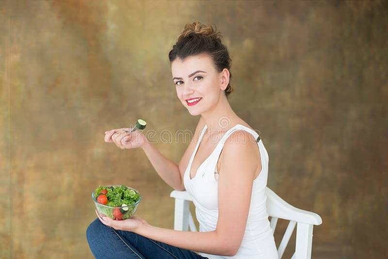 华美的健康妇女坐吃芝麻菜,有机蕃茄,在办公室期间的健康午餐的沙拉一把白色椅子 免版税库存照片