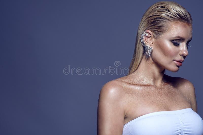 华美的别致的白肤金发的妇女和在她的耳朵的珍贵的袖口画象有湿头发和光亮的艺术性的构成佩带的白色上面的 图库摄影