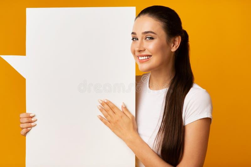 华美的在黄色背景的妇女藏品空白白色讲话泡影 库存照片