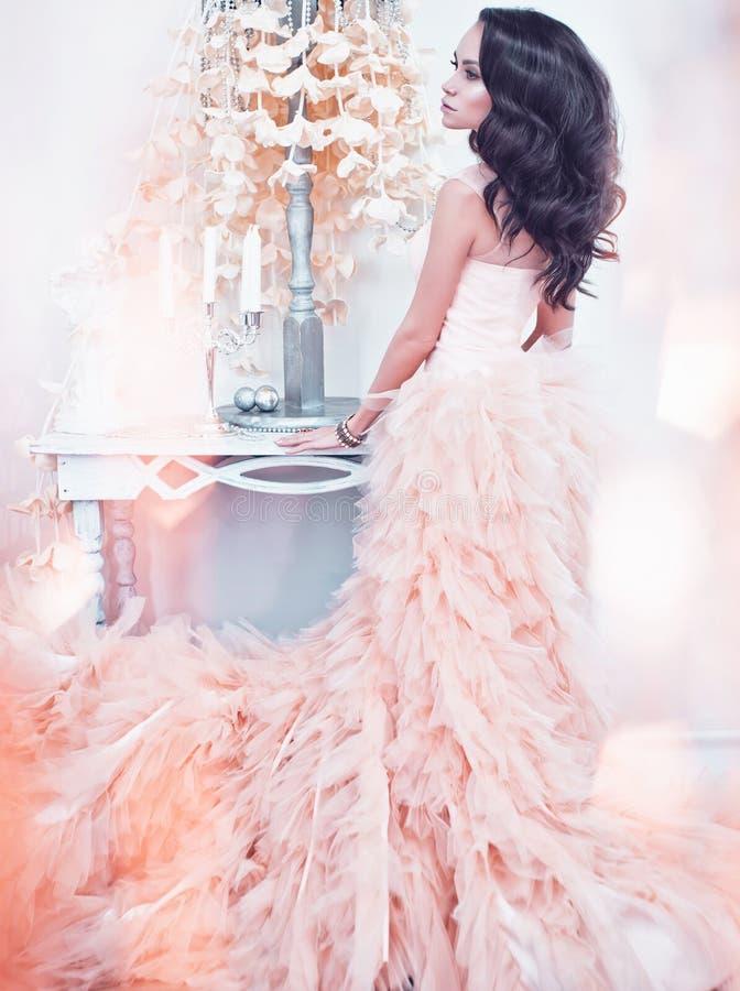 华美的女装设计礼服的美丽的夫人在白色内部 免版税图库摄影