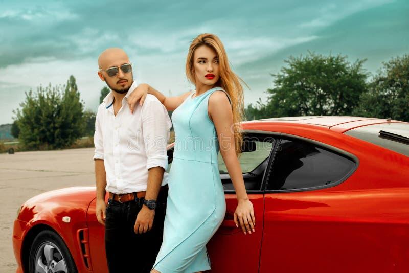 华美的妇女和英俊的人有红色跑车的 免版税库存照片
