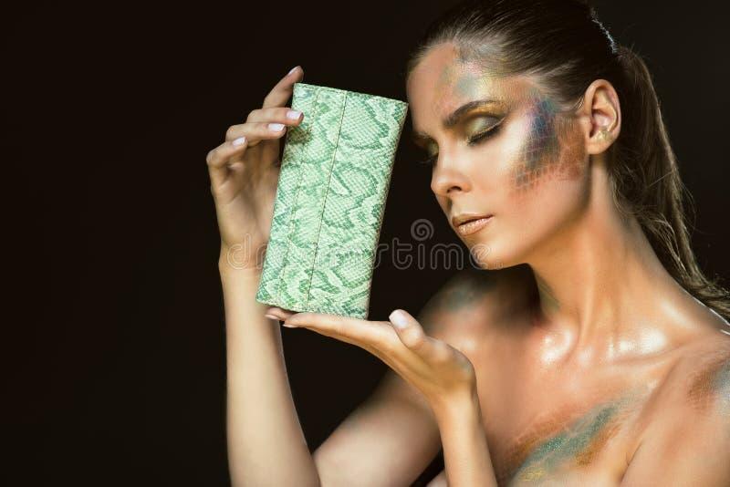 华美的妇女画象的关闭有闭合的眼睛的和艺术性的snakeskin做停滞绿色皮革钱包在她的面孔 库存图片