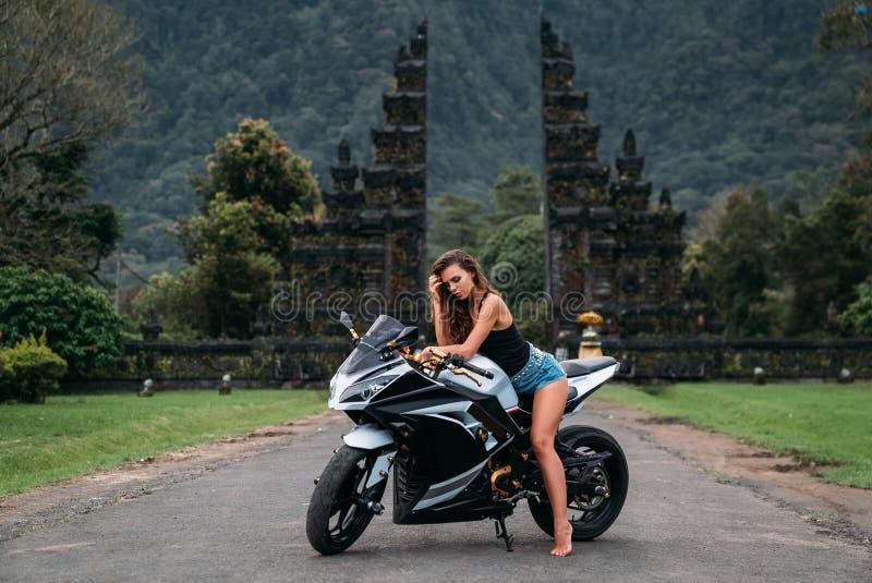 华美的性感的女孩坐在黑白的一辆摩托车 模型在摆在一件黑球衣和牛仔布的短裤穿戴了  图库摄影
