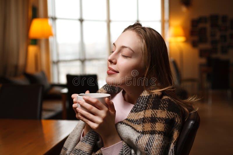 华美的愉快的妇女喝咖啡在咖啡馆背景 被盖的舒适格子花呢披肩 库存照片
