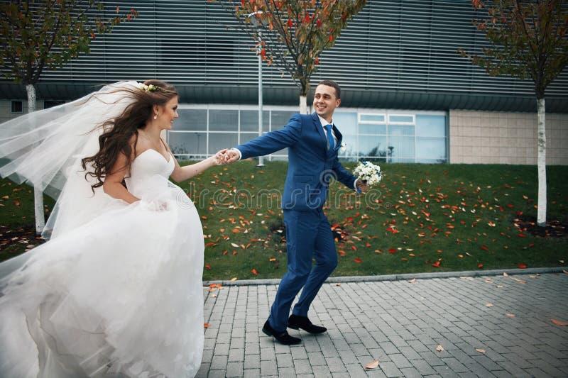 华美的愉快的深色的新娘和典雅的新郎蓝色衣服奔跑的 免版税库存照片